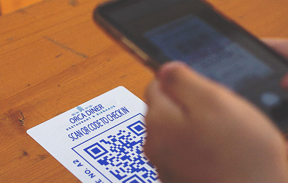 A picture of a person using their phone to check in to a restaurant called Orca Diner by scanning a simple QR code